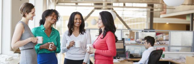 Female work colleagues chatting over coffee in the office