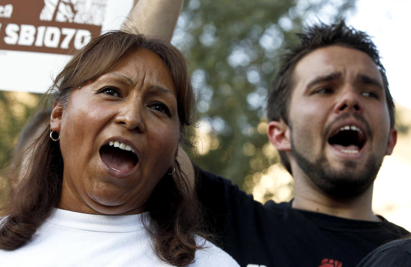 """Maria Cruz, left, and Lincoln Statler chant as they join dozens who rally in front of  U.S. Immigration and Customs Enforcement building, a day after a portion of Arizona's immigration law took effect, Wednesday, Sept. 19, 2012, in Phoenix. Civil rights activists contend will lead to systematic racial profiling, as the protesters chanted """"No papers, no fear.""""(AP Photo/Ross D. Franklin)"""