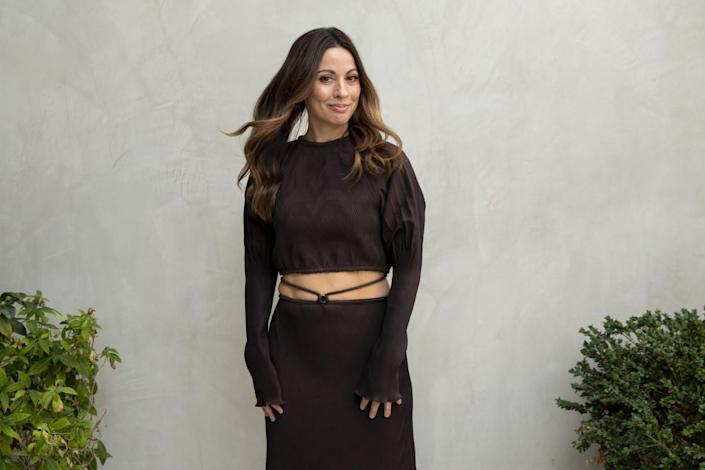 Kay Cannon stands between shrubs before a pale wall.