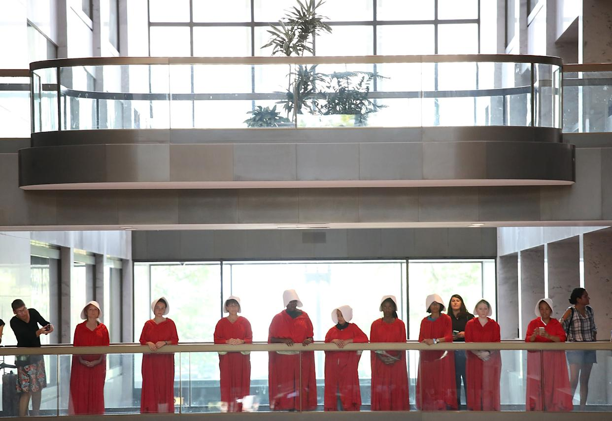 "Protesters dressed in ""The Handmaid's Tale"" costumes stand outside the hearing room where Supreme Court nominee Judge Brett Kavanaugh will testify before the Senate Judiciary Committee during his Supreme Court confirmation hearing. (Photo: Win McNamee/Getty Images)"