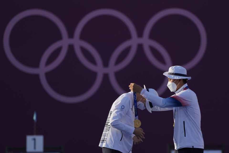First placed South Korea's An San, left, and South Korea's Kim Je Deok receive the gold medals on the podium of a mixed team competition at the 2020 Summer Olympics, Saturday, July 24, 2021, in Tokyo, Japan. (AP Photo/Alessandra Tarantino)