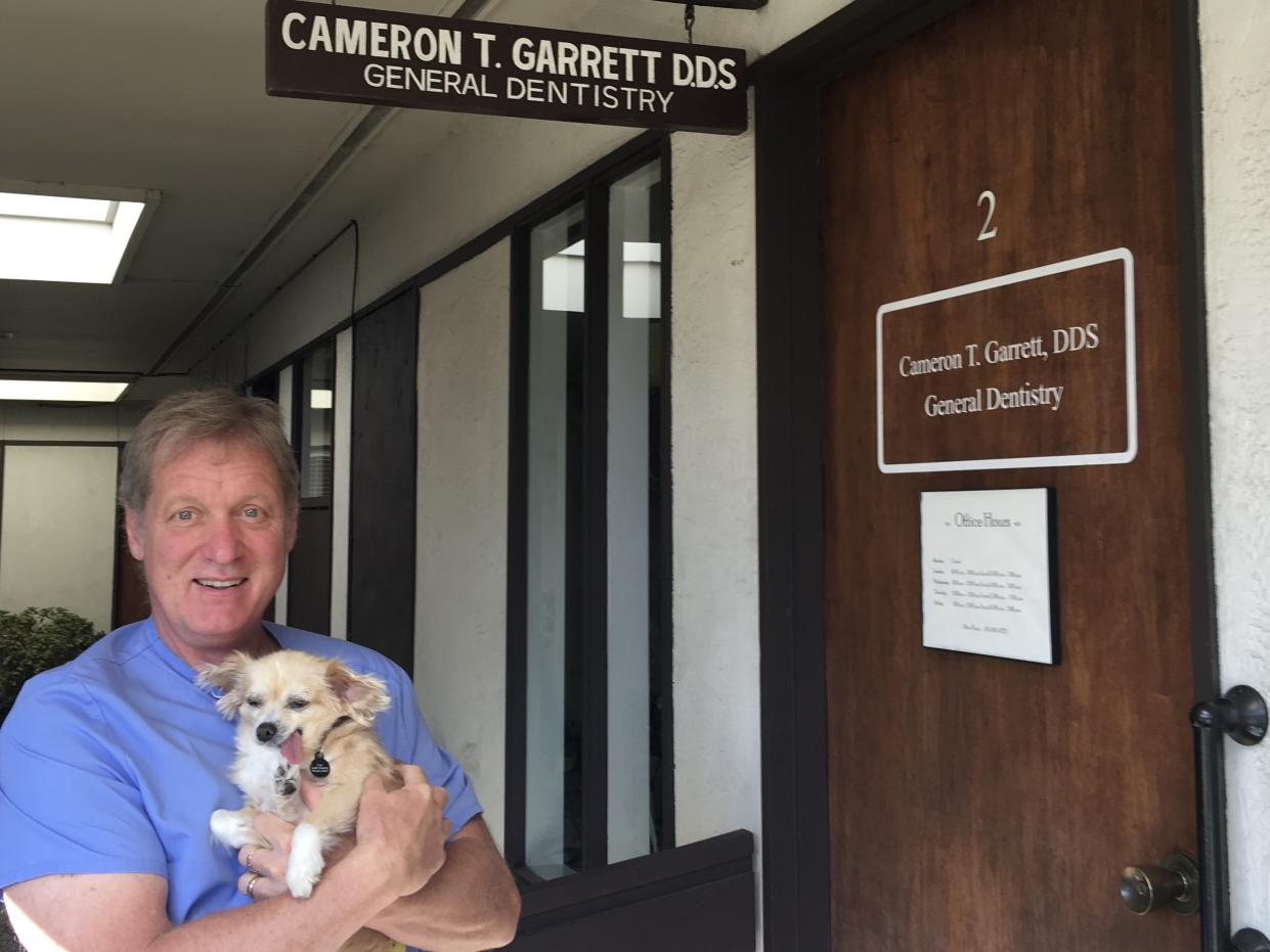 Dr. Cameron Garrett holds Karma, his first dental therapy dog.