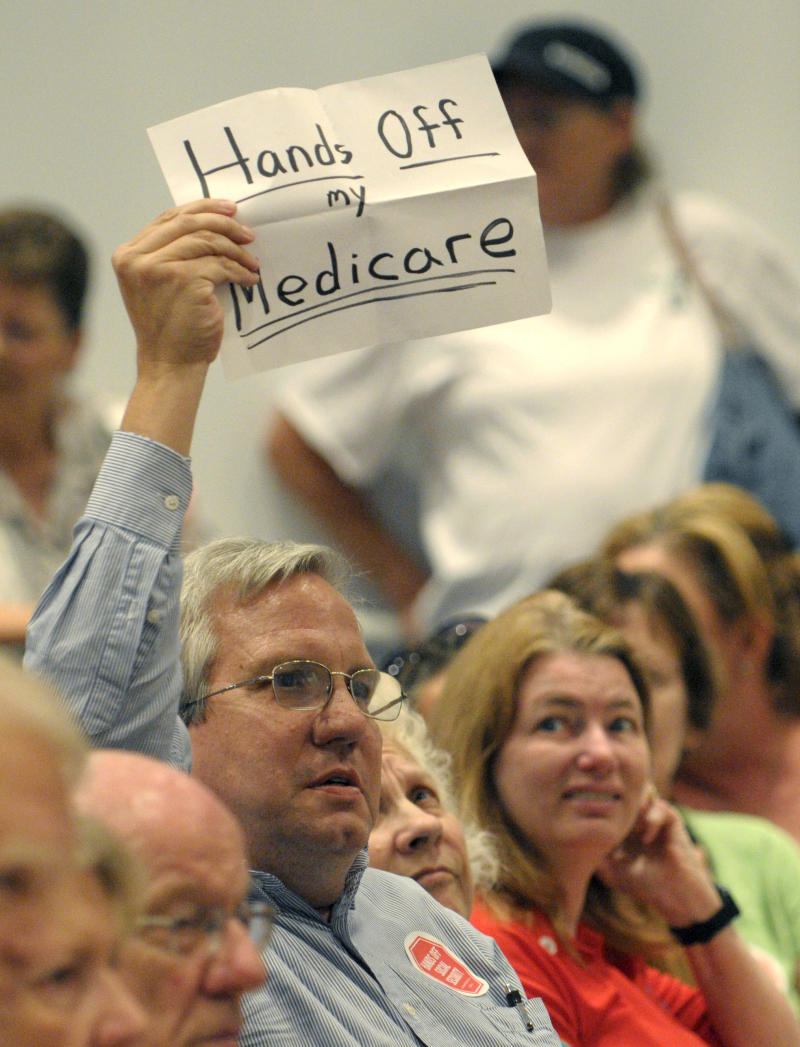 Jim Callahan, 52, of Orlando, raises a sign during a town hall meeting held by Rep. Daniel Webster, R-Fla., in Orlando, Fla., Tuesday, April 26, 2011. Congressional Republicans are getting mixed reviews as they pitch their budget plan to constituents back home.   Webster faced heckling, boos and shouting matches between supporters and opponents during an hour-long meeting.   Webster defended the budget blueprint authored by Ryan that would cut social safety-net programs such as food stamps and Medicaid. (AP Photo/Phelan M. Ebenhack)