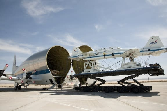 Two retired NASA T-38 trainers mounted on a transport pallet atop a mobile transporter are positioned for loading aboard NASA's Super Guppy prior to ferrying them to El Paso, Texas, for disassembly. Image released March 21, 2013.