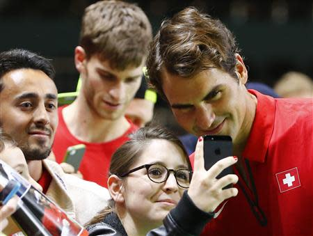 Switzerland's Roger Federer poses with a fan for a selfie after winning his Davis Cup quarter-final tennis match against Andrey Golubev of Kazakhstan in Geneva April 6, 2014. REUTERS/Denis Balibouse