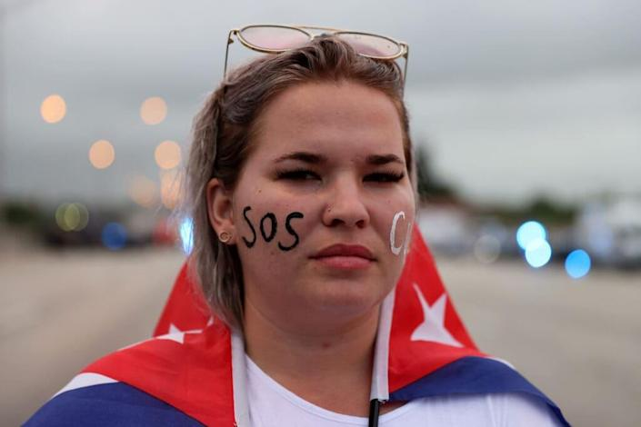 Anabel Alcaz joins with other protesters who shut down part of the Palmetto Expressway as they show their support for the people in Cuba July 13, 2021 in Miami, Florida. (Photo by Joe Raedle/Getty Images)