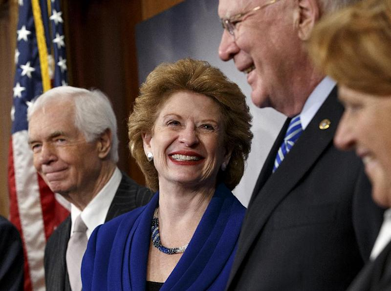 Senate Agriculture Committee Chair Sen. Debbie Stabenow, D-Mich., second from left, celebrates with fellow committee members during a news conference on Capitol Hill in Washington, Tuesday, Feb. 4, 2014, after Congress gave its final approval to a sweeping five-year farm bill. From left are, the committee's ranking member Sen. Thad Cochran, R-Miss., Stabenow, Sen. Patrick Leahy, D-Vt., and Sen. Heidi Heitkamp, D-N.D. (AP Photo/J. Scott Applewhite) (AP Photo/J. Scott Applewhite)