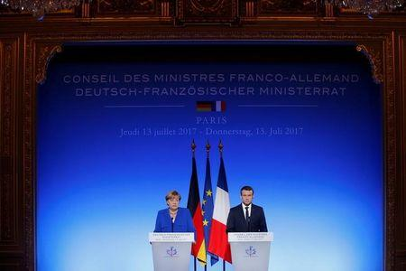French President Emmanuel Macron and German Chancellor Angela Merkel attend a news conference following a Franco-German joint cabinet meeting at the Elysee Palace in Paris