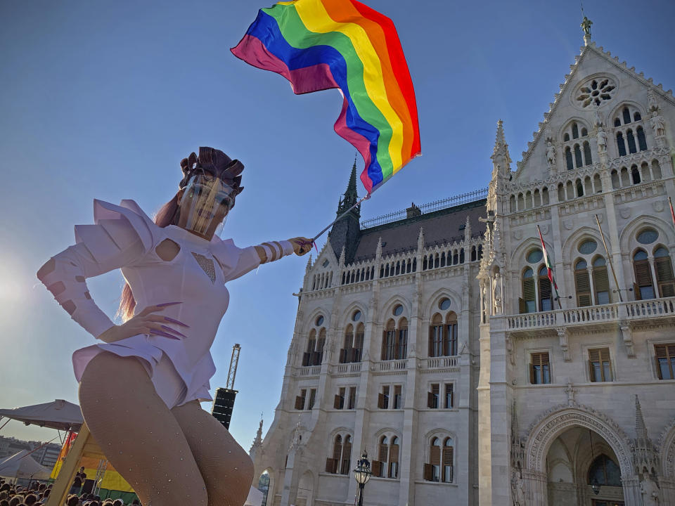 FILE - In this June 14, 2021 file photo a drag queen waves a rainbow flag during an LGBT rights demonstration in front of the Hungarian Parliament building in Budapest, Hungary. Populist Prime Minister Viktor Orban has long used soccer to advance his right-wing politics, and now widespread international criticism of a new Hungarian law that is seen as targeting the LGBT community has turned this month's Euro 2020 tournament into a major stage for his challenge to Europe's liberal values. (AP Photo/Bela Szandelszky, File)
