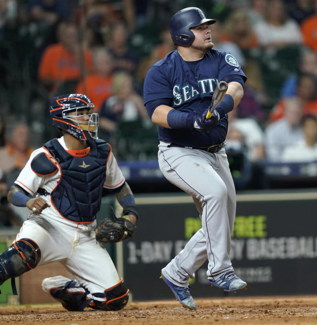 Seattle Mariners' Daniel Vogelbach, right, hits a grand slam as Houston Astros catcher Martin Maldonado watches during the eighth inning of a baseball game Monday, Sept. 17, 2018, in Houston. (AP Photo/David J. Phillip)