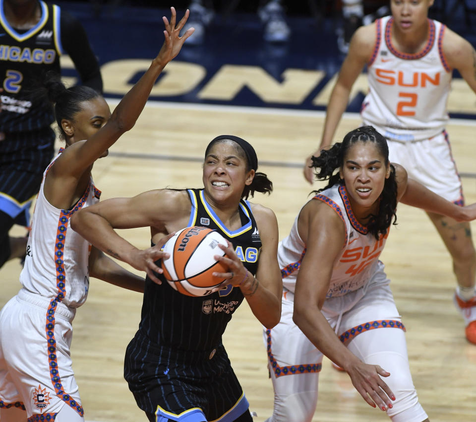 Chicago Sky forward Candace Parker, center, makes her move against the defense of Connecticut Sun forward DeWanna Bonner, left, and center Brionna Jones in the second half of a WNBA basketball game Sunday, June 27, 2021, in Uncasville, Conn. (Sean D. Elliot/The Day via AP)