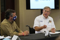 Sen. Ted Cruz, R-Texas, and Texas Gov. Greg Abbott talk during a briefing with President Donald Trump about Hurricane Laura with first responders at the emergency operations center Saturday, Aug. 29, 2020, in Orange, Texas. (AP Photo/Alex Brandon)
