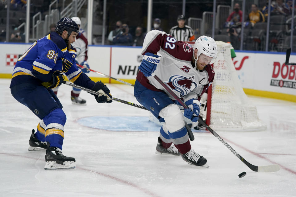 Colorado Avalanche's Gabriel Landeskog (92) handles the puck as St. Louis Blues' Ryan O'Reilly (90) defends during the second period in Game 4 of an NHL hockey Stanley Cup first-round playoff series Sunday, May 23, 2021, in St. Louis. (AP Photo/Jeff Roberson)