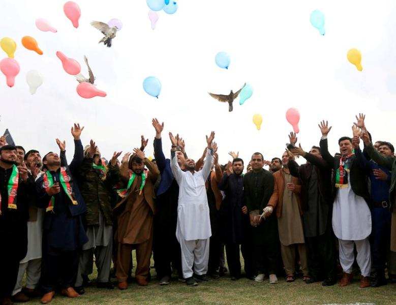 FILE PHOTO: Afghan men celebrate in anticipation of the U.S-Taliban agreement to allow a U.S. troop reduction and a permanent ceasefire, in Jalalabad