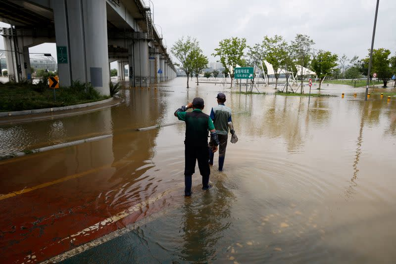 Workers look at a flooded Han River park in Seoul