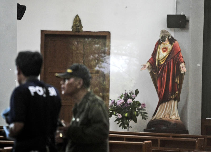 In this image shot through a glass window, police investigators examine the interior of St. Lidwina Church that was damaged following an attack in Sleman, Yogyakarta province, Indonesia, Sunday, Feb. 11, 2018. Police shot a sword-wielding man who attack the church during a mass, injuring a number of people including a German priest. The reason for the attack Sunday morning was not immediately clear. (AP Photo)