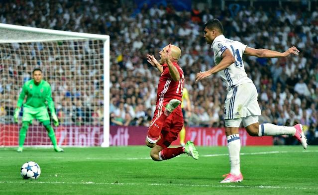 Bayern Munich's midfielder Arjen Robben (L) is fouled by Real Madrid's Brazilian midfielder Casemiro during the UEFA Champions League quarter-final second leg football match Real Madrid vs FC Bayern Munich on April 18, 2017 (AFP Photo/GERARD JULIEN)