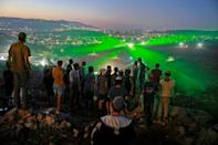 Israeli settlers in the wildcat outpost of Eviatar look on as Palestinian protestors flash laser beams towards them from the nearby village of Beita