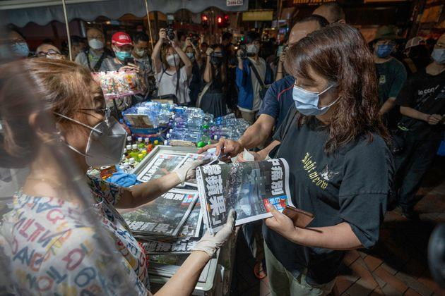 HONG KONG, CHINA - 2021/06/24: <p>A female supporter seen purchasing a copy of the final edition of the Apple Daily newspaper at a newsstand in Mong Kok.</p><p>Pro-democracy newspaper Apple Daily will cease operation from 24th June after authorities used a national security law to arrest its top editors and freeze company assets. </p>. (Photo by Geovien So/SOPA Images/LightRocket via Getty Images) (Photo: SOPA Images via Getty Images)