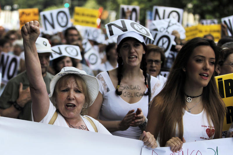 """Protestors shout slogans as hold a banner reading """"no financial cuts"""" during a demonstration against government-imposed austerity measures and labor reforms in the public healthcare sector in Madrid, Spain, Sunday, July 21, 2013. Madrid residents and medical workers angered by budget cuts and plans to part privatize bits of their cherished national health service protested on the streets Sunday. (AP Photo/Andres Kudacki)"""