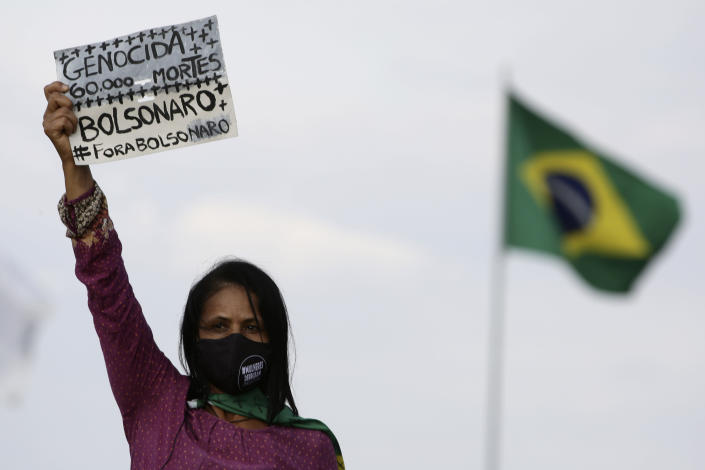 """A women's movement activist holds a sign that reads in Portuguese """"Genocide 60 thousand deaths, Bolsonaro out,"""" during a protest against the government's inefficiency in the face of the new coronavirus pandemic and the ongoing police brutality against blacks, in front of the National Congress, in Brasilia, Brazil, Thursday, July 2, 2020. (AP Photo/Eraldo Peres)"""