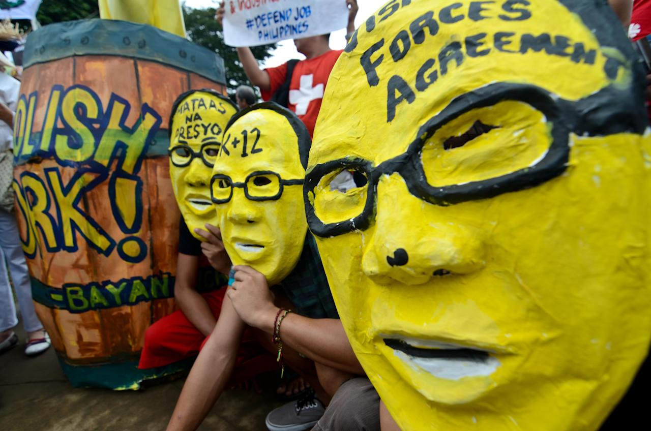 """MANILA, PHILIPPINES - AUGUST 26: Protestors wearing caricature masks of Philippine president Benigno Aquino III attend a protest against the misuse of Philippine state funds during a huge rally in Luneta Park on August 26, 2013 in Manila, Philippines. The calls for a protest, which began in social media, snowballed into a demonstration after a whistleblower exposed a scandal involving billions of pesos from the Priority Development Assistance Fund (PDAF) were being diverted to a select group of politicians through a number of bogus Non Government Organizations (NGOs) which allegedly siphoned off billions of pesos for ghost projects. The fund is money allocated for lawmakers to be used in development projects. Critics see it as funding """"pork barrel"""" projects which have traditionally been a source of corruption. (Photo by Dondi Tawatao/Getty Images)"""