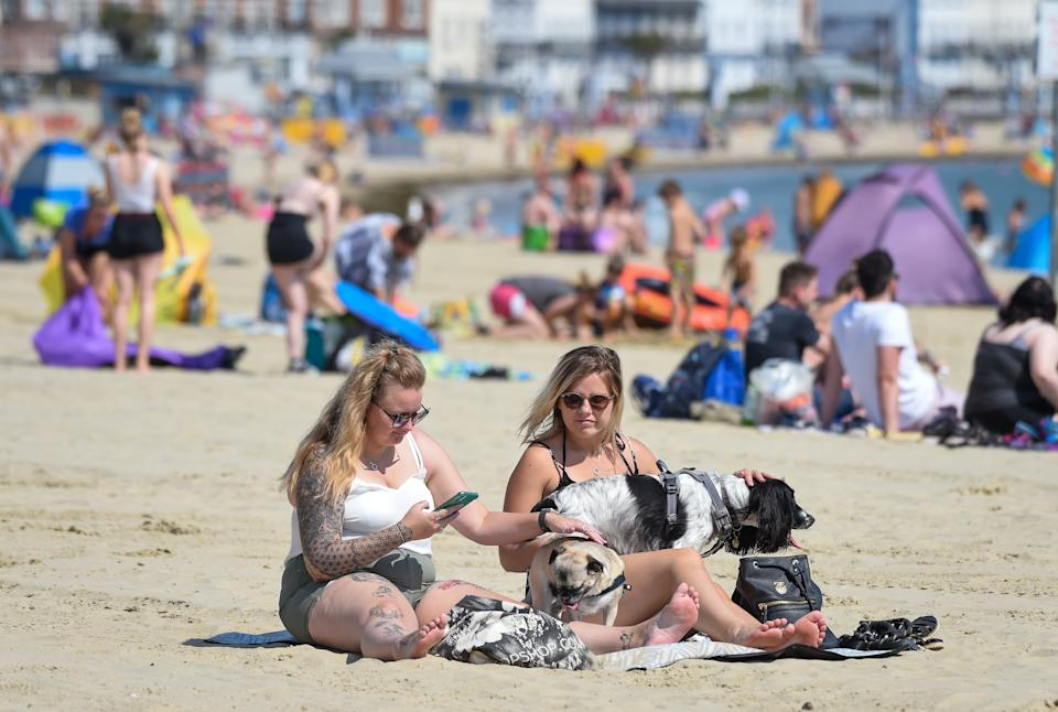 WEYMOUTH, ENGLAND - JUNE 24: Visitors enjoy the hot weather on the beach on June 24, 2020 in Weymouth, United Kingdom. The UK is experiencing a summer heatwave, with temperatures in many parts of the country expected to rise above 30C and weather warnings in place for thunderstorms at the end of the week. (Photo by Finnbarr Webster/Getty Images)