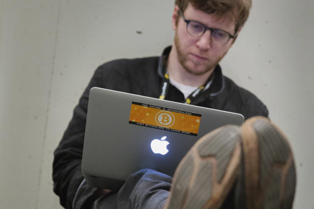 A bitcoin sticker is seen on a man's computer at the Inside Bitcoins Conference in New York, April 8, 2014. (REUTERS/Lucas Jackson)