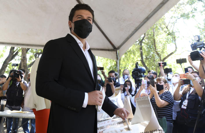Samuel Garcia casts his ballot during mid-term elections in Monterrey, Nuevo Leon state, Mexico, Sunday, June 6, 2021. Garcia, 33, is a baby-faced former senator whose blond wife, YouTuber Mariana Rodríguez, is better known for posting videos of herself giving makeup tutorials or clutching a small dog. (AP Photo/Roberto Martinez)