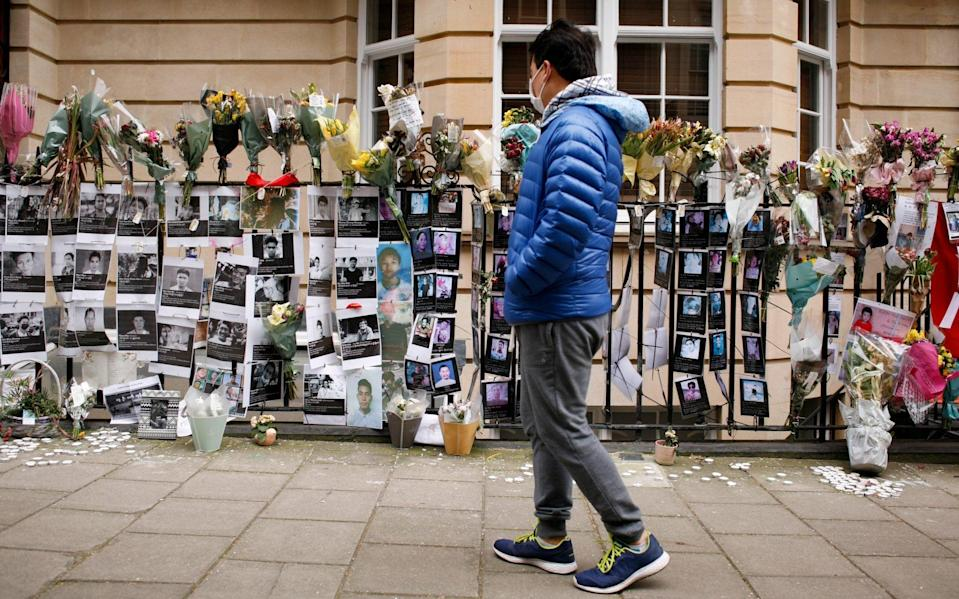 A man looks at floral tributes and pictures of the victims of pro-democracy protests attached to railings outside the embassy of Myanmar in London - Anadolu