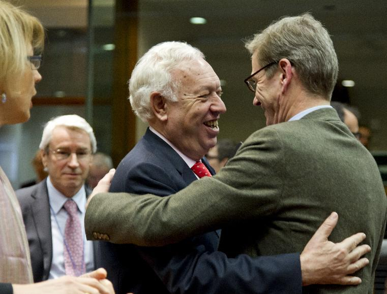 German Foreign Minister Guido Westerwelle, right, greets Spain's Foreign Minister Jose Manuel Garcia-Margallo, center, during a meeting of EU foreign ministers at the EU Council building in Brussels on Monday, Dec. 10, 2012. The 27 EU foreign ministers will discuss the situation in Syria, where activists say more than 40,000 people have died. (AP Photo/Virginia Mayo)
