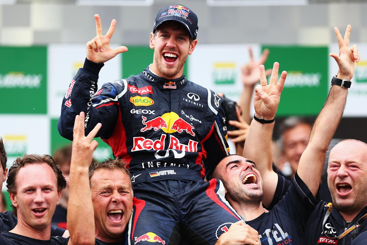 SAO PAULO, BRAZIL - NOVEMBER 25:  Sebastian Vettel of Germany and Red Bull Racing celebrates with team mates on the podium as he finishes in sixth position and clinches the drivers world championship during the Brazilian Formula One Grand Prix at the Autodromo Jose Carlos Pace on November 25, 2012 in Sao Paulo, Brazil.  (Photo by Paul Gilham/Getty Images)