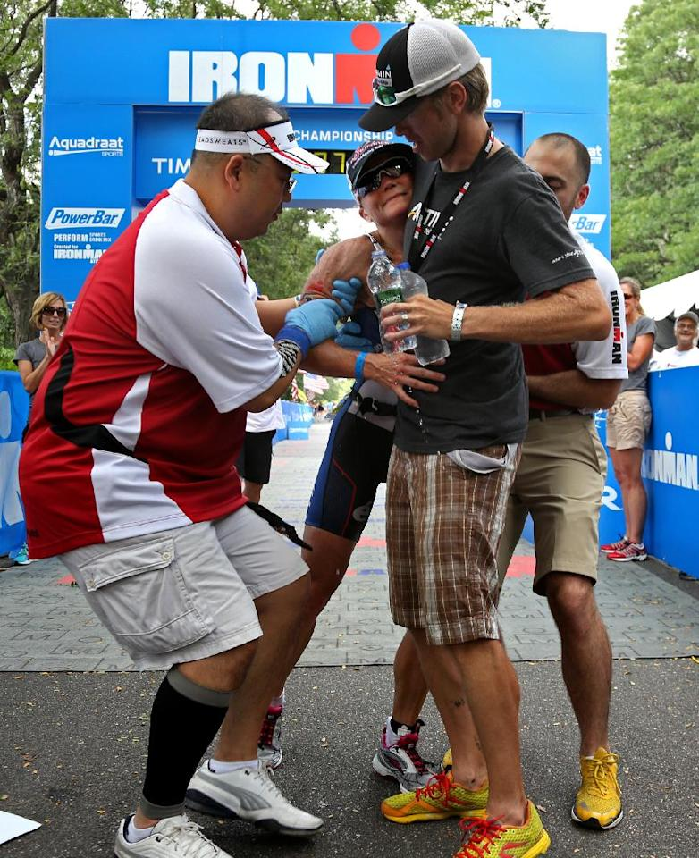 Mary Beth Ellis collapses briefly after crossing the finish line to win women's division of the Ironman U.S. Championship triathlon in New York, Saturday, Aug. 11, 2012. Ellis recovered quickly and was able to walk under her own power. (AP Photo/Craig Ruttle)