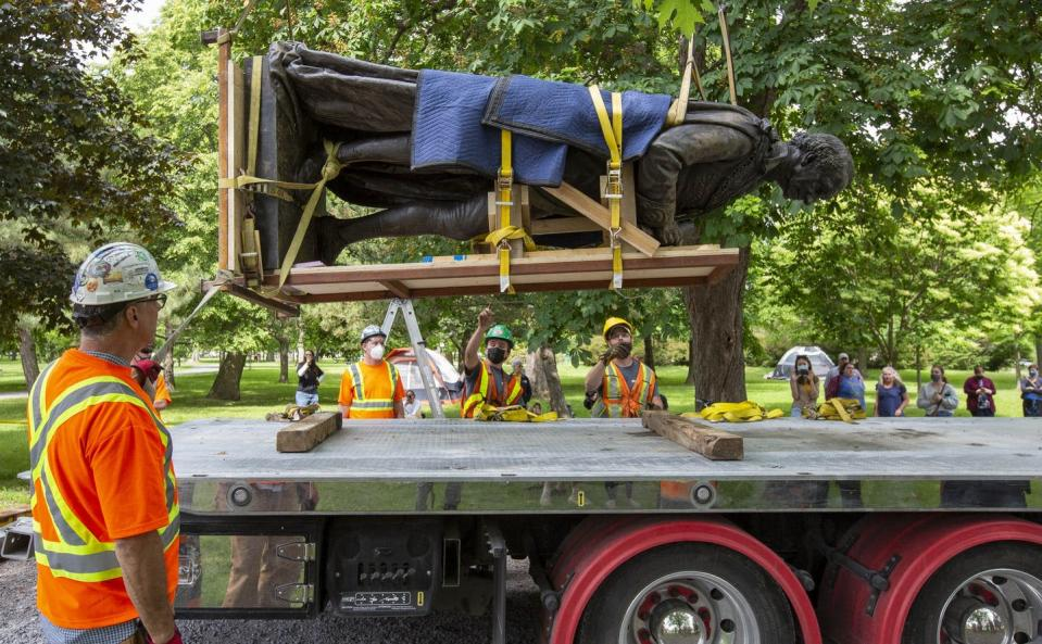"""<span class=""""caption"""">Workers lower a a statue of Canada's first prime minister, John A. Macdonald, onto a truck as a crowd watches in Kingston, Ont., June 18, 2021. </span> <span class=""""attribution""""><span class=""""source"""">THE CANADIAN PRESS/Lars Hagberg</span></span>"""