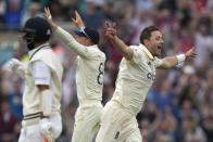 England's Ollie Robinson, right celebrates taking the wicket of India's Cheteshwar Pujara, left, on day three of the fourth Test match at The Oval cricket ground in London, Saturday, Sept. 4, 2021. (AP Photo/Kirsty Wigglesworth)