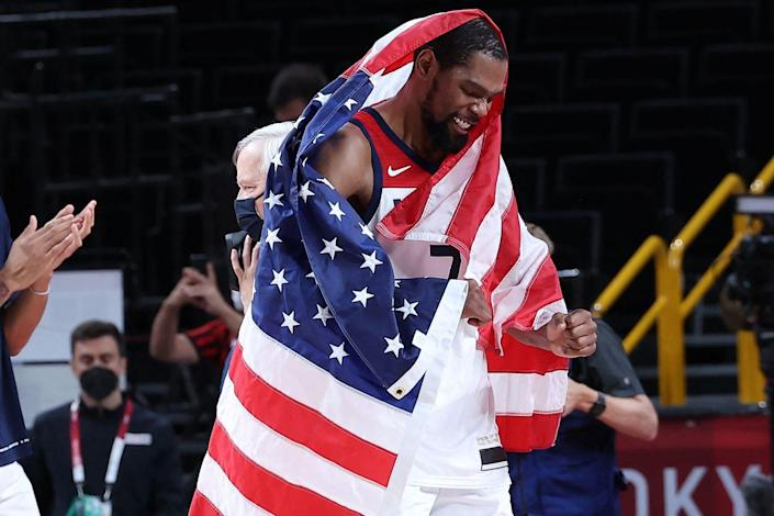 <p>USA's Kevin Durant carries national flag while celebrating his team's win in the men's final basketball match against France.</p>