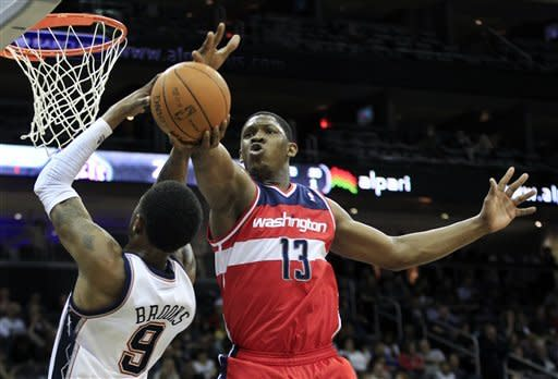 Washington Wizards' Kevin Seraphin, (13), of France, blocks a shot by New Jersey Nets' Deron Williams (8) during the first quarter of an NBA basketball game in Newark, N.J., Friday, April 6, 2012. (AP Photo/Mel Evans)