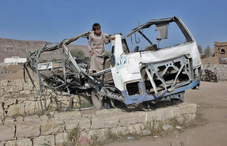 A Yemeni boy on September 4, 2018 stands in the wreckage of the bus which was hit by a Saudi-led coalition air strike