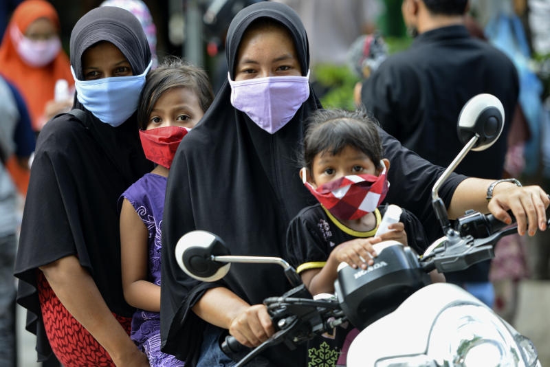 People wearing face masks, amid concerns of the COVID-19 coronavirus, commute on a street in Banda Aceh on April 7, 2020. (Photo by CHAIDEER MAHYUDDIN / AFP) (Photo by CHAIDEER MAHYUDDIN/AFP via Getty Images)