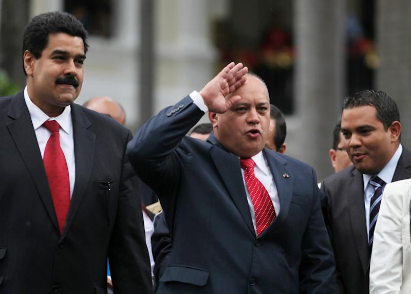 National Assembly President Diosdado Cabello, center, gestures to supporters of President Hugo Chavez as Vice President Nicolas Maduro, left, looks on after a session by lawmakers at the National Assembly in Caracas, Venezuela, Saturday, Jan. 5, 2013. Allies of President Hugo Chavez on Saturday chose to keep Diosdado as National Assembly president who is the next in line to step in as a caretaker leader in some circumstances. Just five days remain until Chavez's scheduled inauguration on Thursday, and government officials are suggesting the swearing-in could be delayed as the president fights a severe respiratory infection after cancer surgery in Cuba. (AP Photo/Fernando Llano)