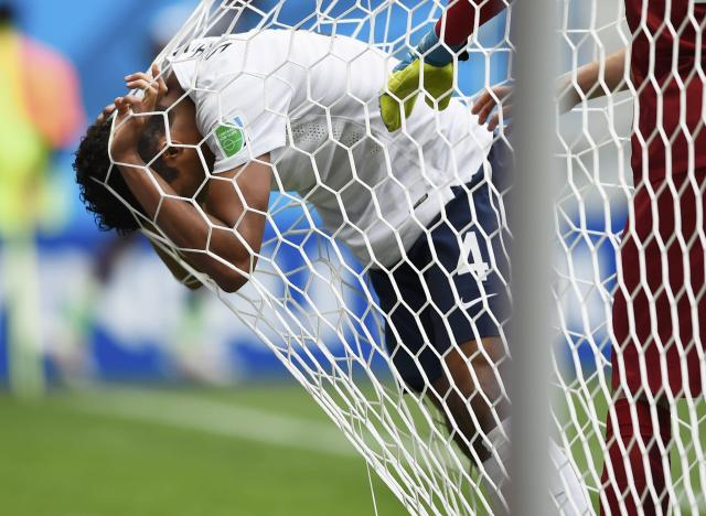 France's Raphael Varane reacts against the goal net to getting hit in the face by the ball during their 2014 World Cup round of 16 game against Nigeria at the Brasilia national stadium in Brasilia June 30, 2014. REUTERS/Dylan Martinez (BRAZIL - Tags: SOCCER SPORT WORLD CUP TPX IMAGES OF THE DAY)