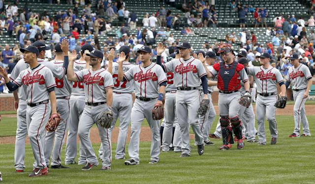 The Atlanta Braves celebrate their 9-5 win over the Chicago Cubs after a baseball game on Friday, Sept. 20, 2013, in Chicago. (AP Photo/Charles Rex Arbogast)
