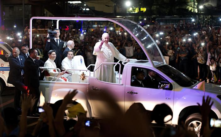 Pope Francis waves to Filipino Catholics as his motorcade passes by in Manila on January 15, 2015 (AFP Photo/Noel Celis)