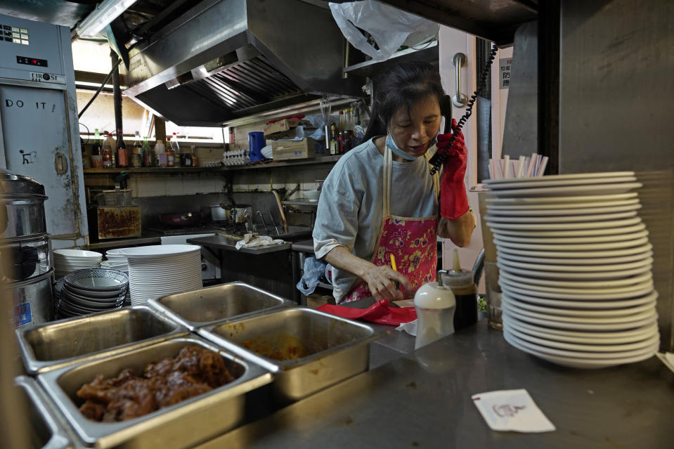 A restaurant employee takes phone orders at a Chinese food court in Hong Kong, Wednesday, July 29, 2020. Hong Kong has banned dining-in at restaurants completely on Wednesday and make it mandatory to wear masks in all public places, as the city battles its worst coronavirus outbreak to date. (AP Photo/Vincent Yu)