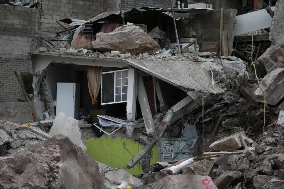 Boulders and debris that plunged from a mountainside rest atop homes in Tlalnepantla, on the outskirts of Mexico City, Saturday, Sept. 11, 2021. A section of a mountain on the outskirts of Mexico City gave way Friday, plunging rocks the size of small homes onto a densely populated neighborhood and leaving at least one person dead and 10 others missing. (AP Photo/Ginnette Riquelme)