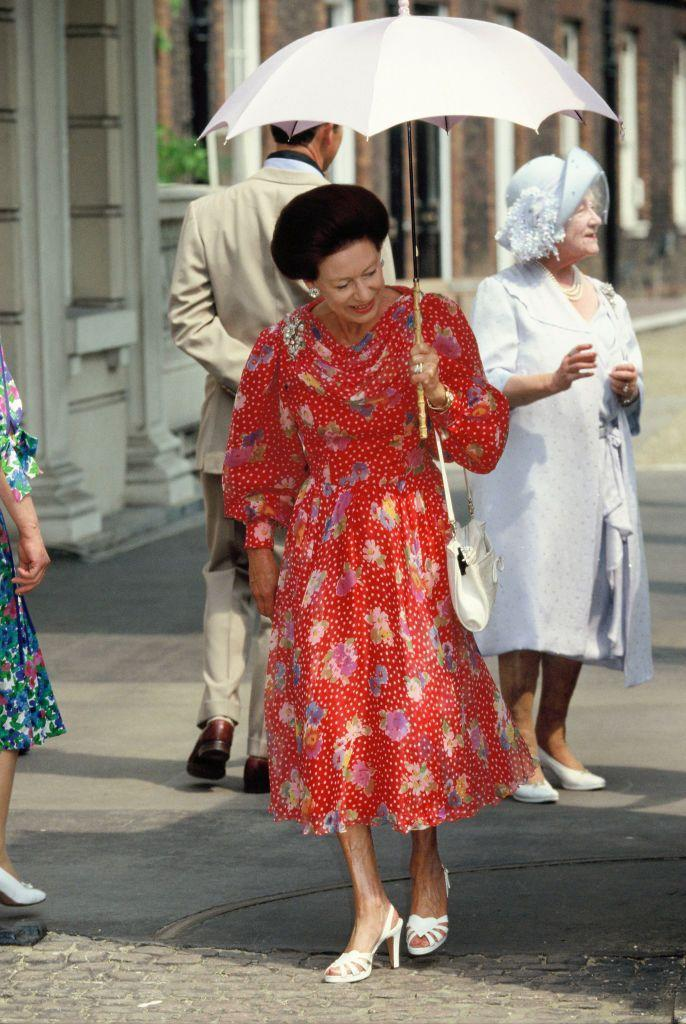 <p>Princess Margaret wore a polka dot-clad dress with a cinched waist and draped neckline for the Queen Mother's 90th birthday celebration in August 1990. A parasol and strappy heels completed the look. </p>