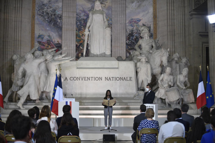 French President Emmanuel Macron, right, listens to a young girl delivering her speech during a ceremony to celebrate the 150th anniversary of the proclamation of the Republic, at the Pantheon monument, Friday Sept.4. 2020 in Paris. (Julien de Rosa, Pool via AP)