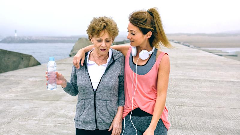Senior woman and young woman walking outdoors by sea pier.