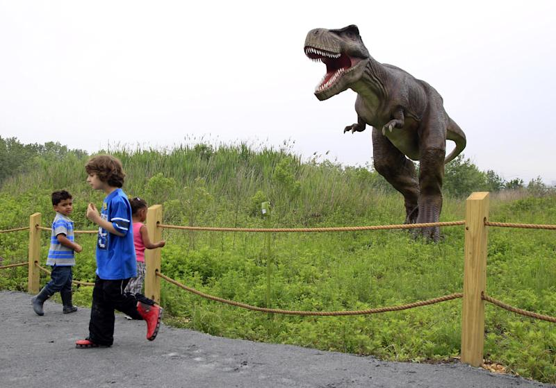 Children watch and react as a Tyrannosaurus T-Rex moves and growls in an inter-active display at Field Station Dinosaurs in Secaucus, N.J., Friday, May 25, 2012. There will be 31 types of life-sized dinosaurs displayed at the Jurassic expedition that opens Saturday, May 26. (AP Photo/Mel Evans)
