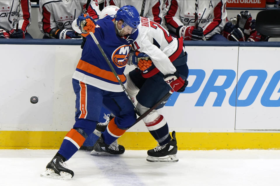 New York Islanders defenseman Adam Pelech (3) checks Washington Capitals right wing Garnet Hathaway (21) against the boards during the first period of an NHL hockey game Thursday, April 22, 2021, in Uniondale, N.Y. (AP Photo/Kathy Willens)